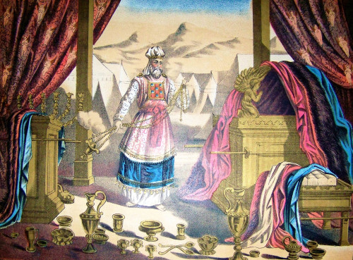 Here the High Priest is pictured in his priestly garments, surrounded by the furniture of the Tabernacle. [Image: Holman Bible / Wiki Commons]