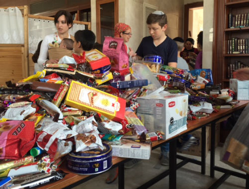 Children in Jerusalem pack Purim treats (Mishloach Manot) for children in orphanages (Photo: Courtesy)